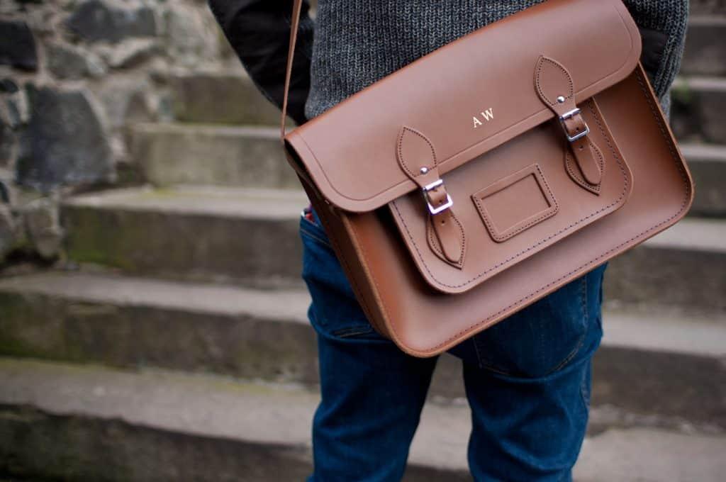 Imagem de pessoa caminhando com uma pasta executiva de couro marrom.