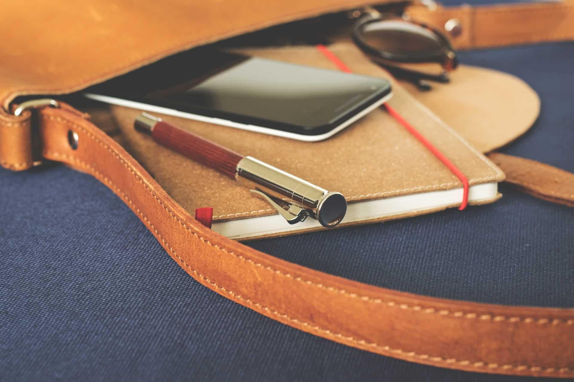 Imagem de pasta executiva de couro marrom com celular, caneta e agenda em destaque.