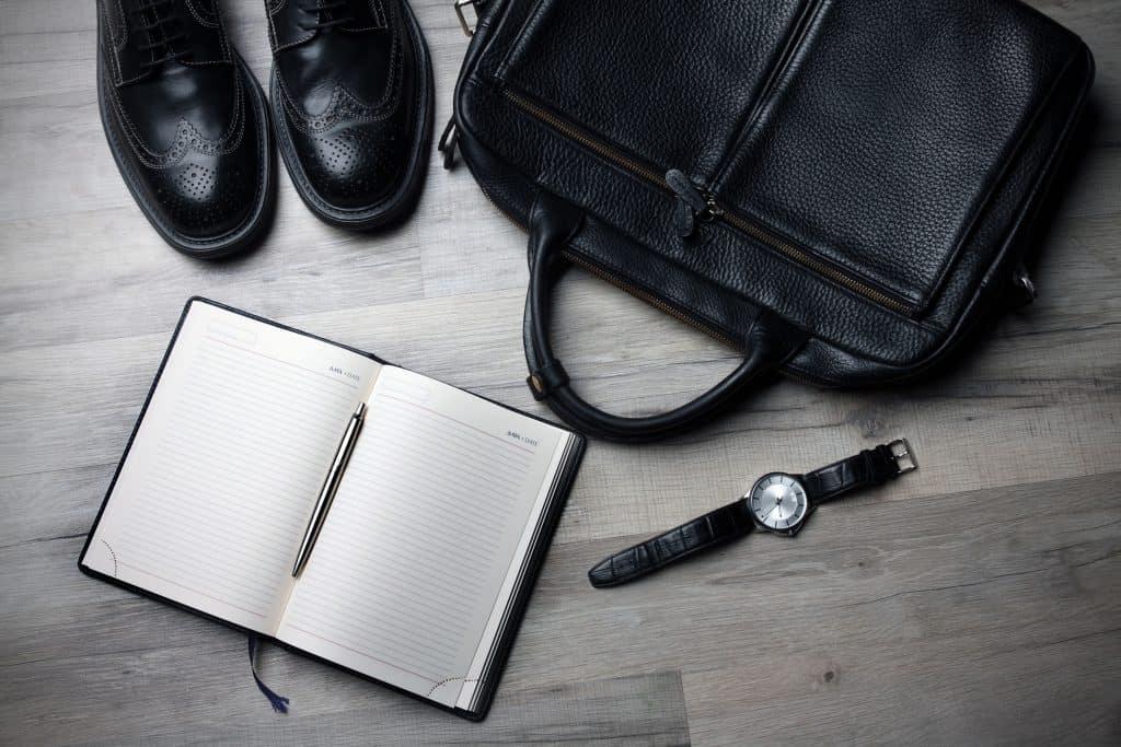 Imagem de pasta executiva, agenda com caneta, relógio e par de sapato.