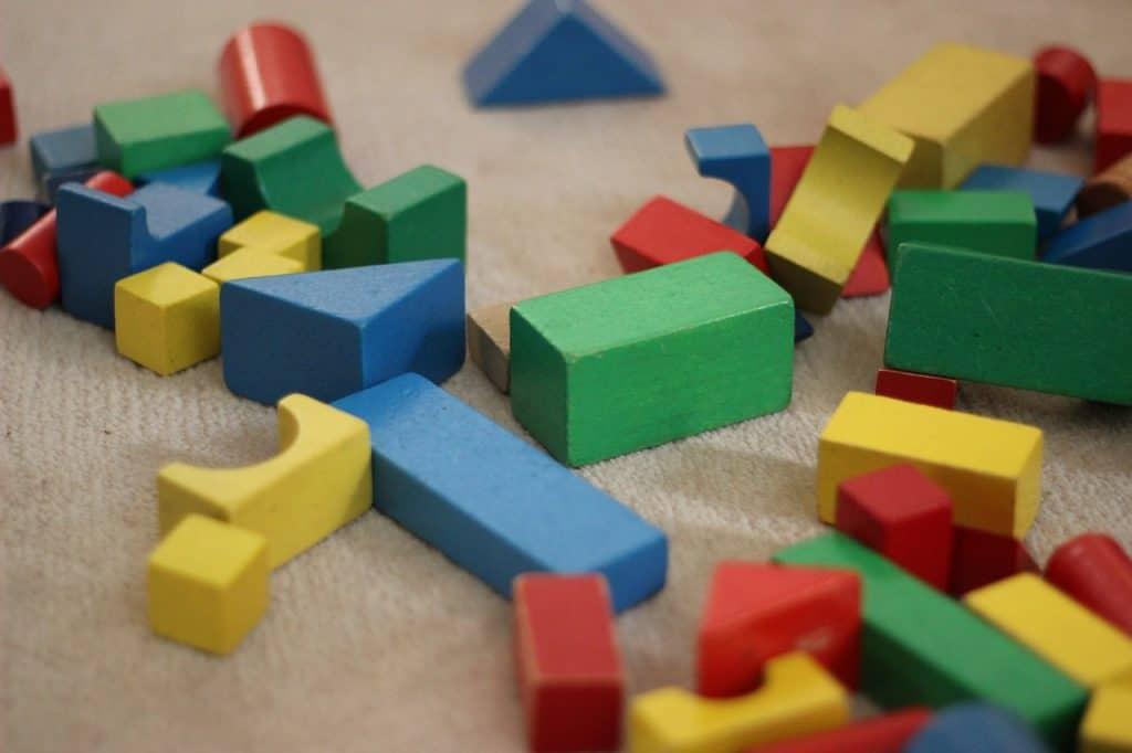 Na foto diversas peças geométricas coloridas de brinquedo.