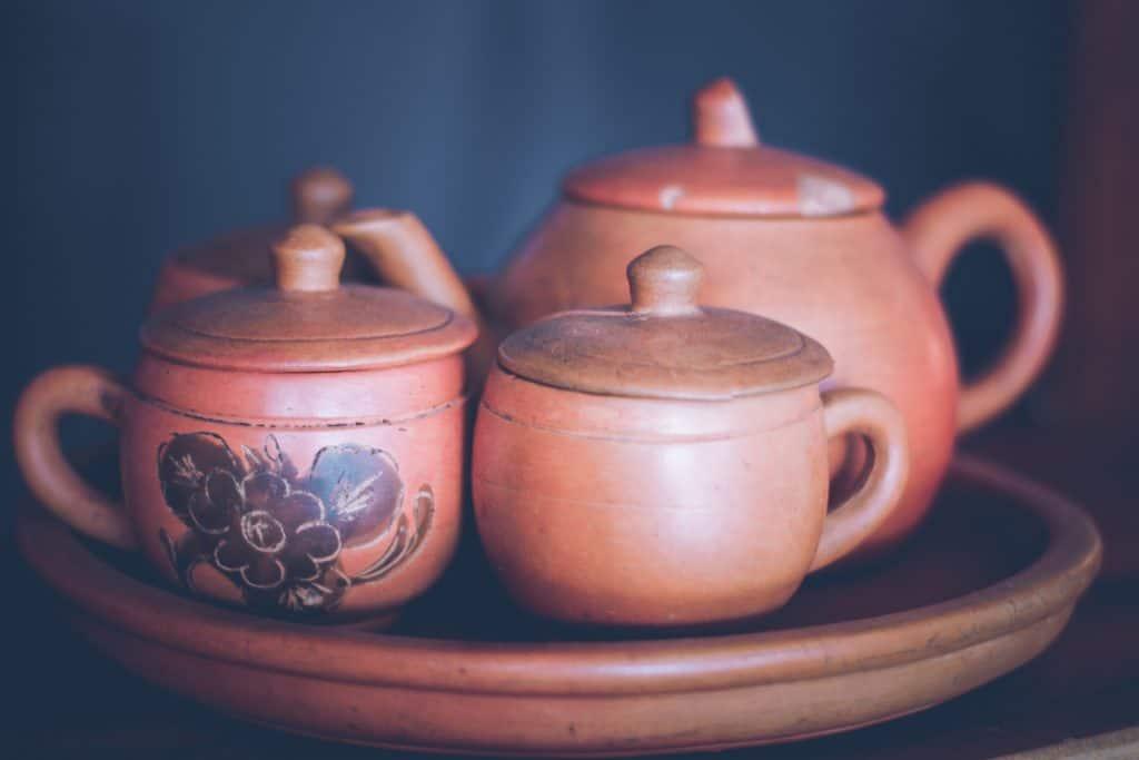 Jogo de chá com açucareiro em cerâmica crua com fundo escuro.