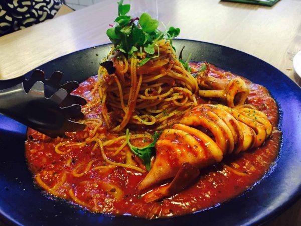 Pegador de macarrão apoiado em prato de espaguete com molho ao sugo, frutos do mar e ervas.