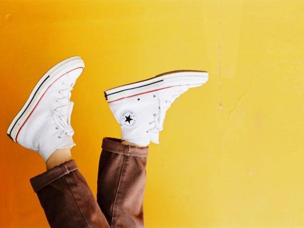 Na foto dois pés usando tênis all star branco de cano alto em frente a uma parede amarela de ponta cabeça.