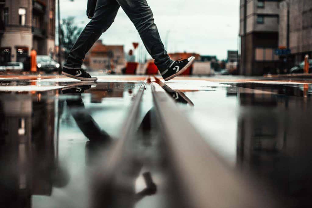 Na foto um homem caminhando de All Star por uma rua.