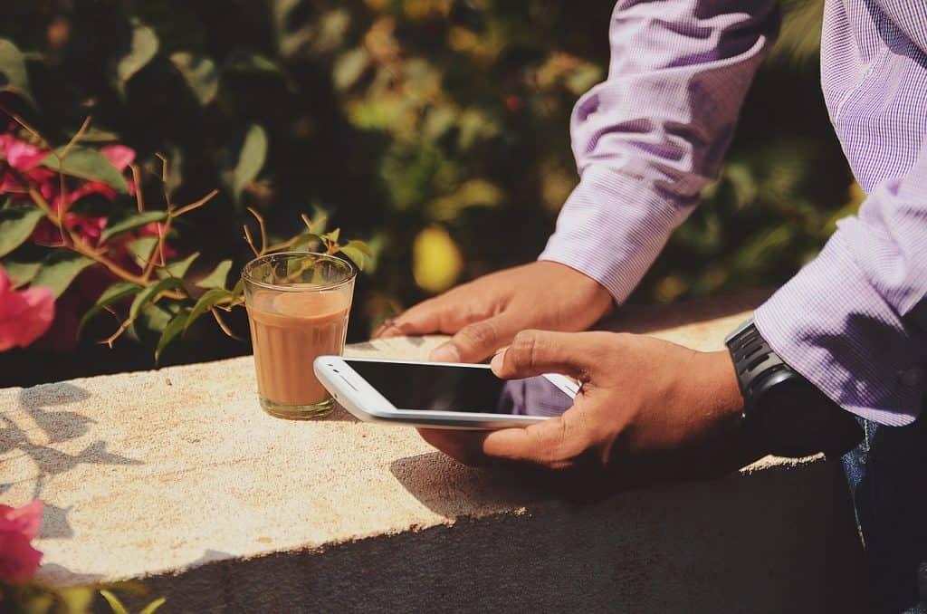 Detalhe de mãos de um homem acessando o celular.