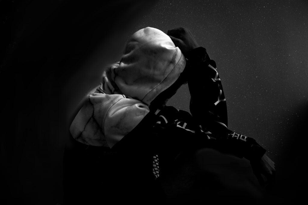 Imagem mostra uma pessoa sentada, usando um moletom, com o capuz cobrindo o seu rosto.