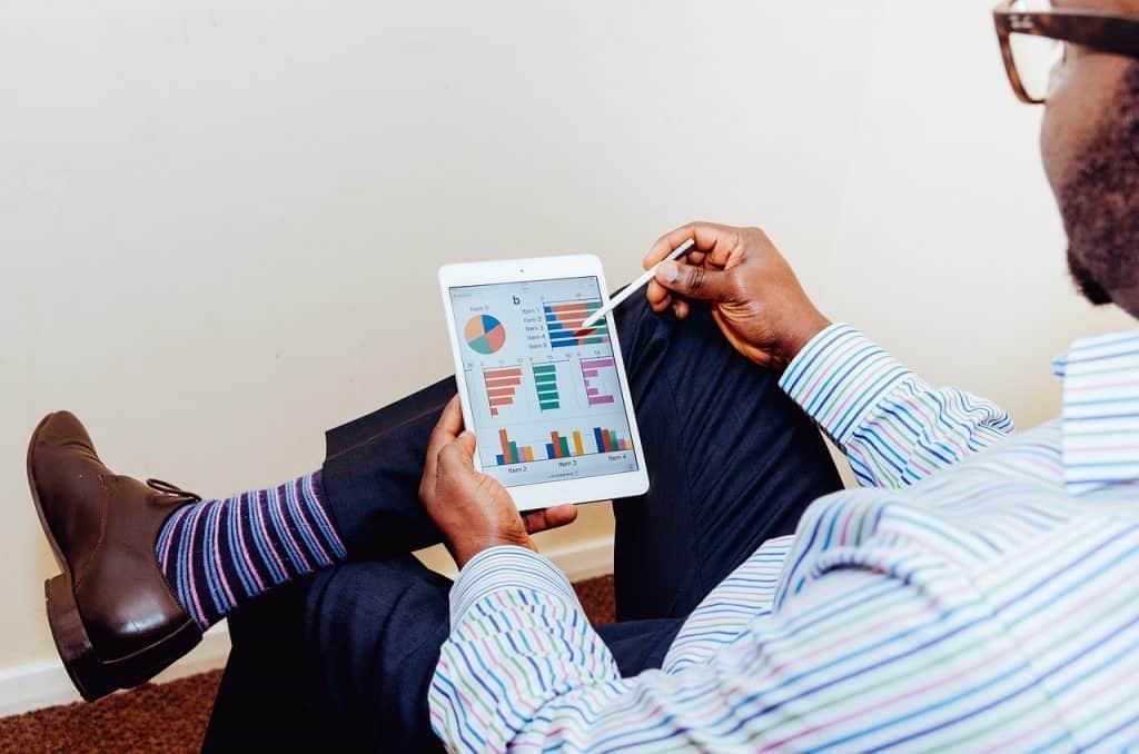 Na foto um homem sentado em uma cadeira com um tablet na mão olhando gráficos.