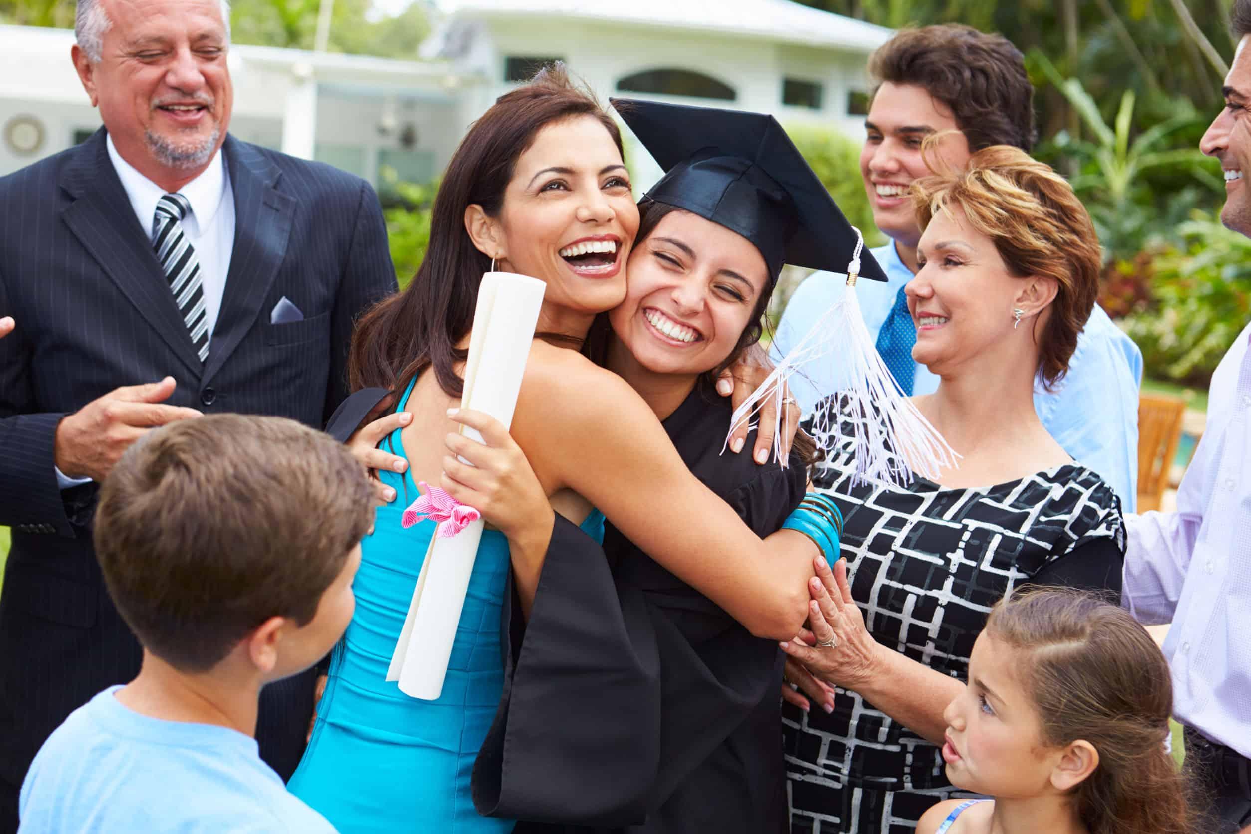 Na foto algumas pessoas ao redor de uma mulher abraçando uma formanda.