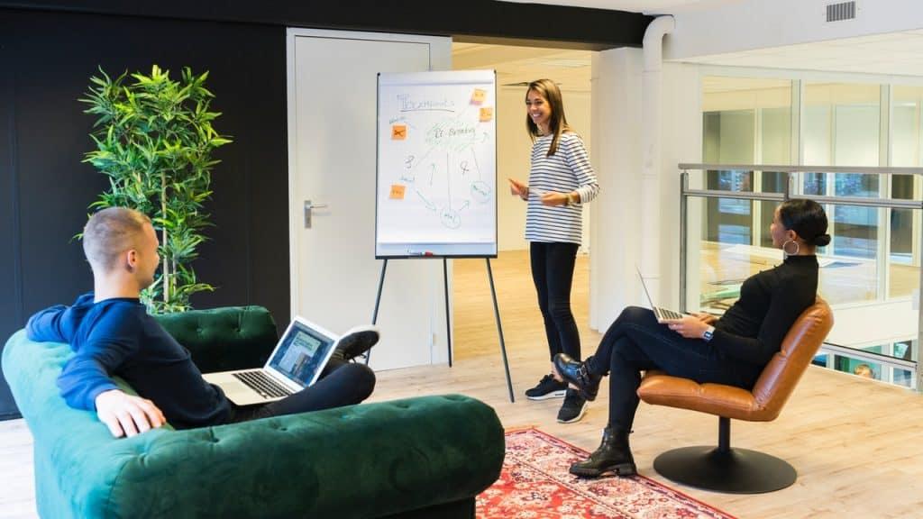 Na foto três pessoas fazendo uma reunião com um flip chart no meio da sala.