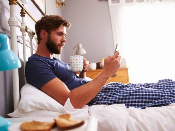 Imagem de um homem sentado na cama, de pijama e mexendo no celular.