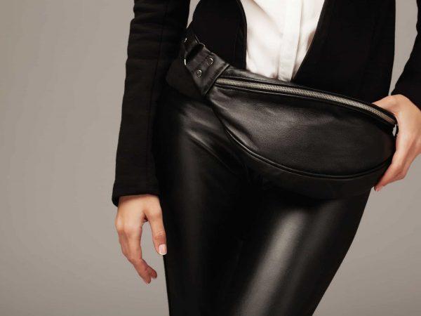 Na foto uma mulher com uma pochete de couro preta na cintura.