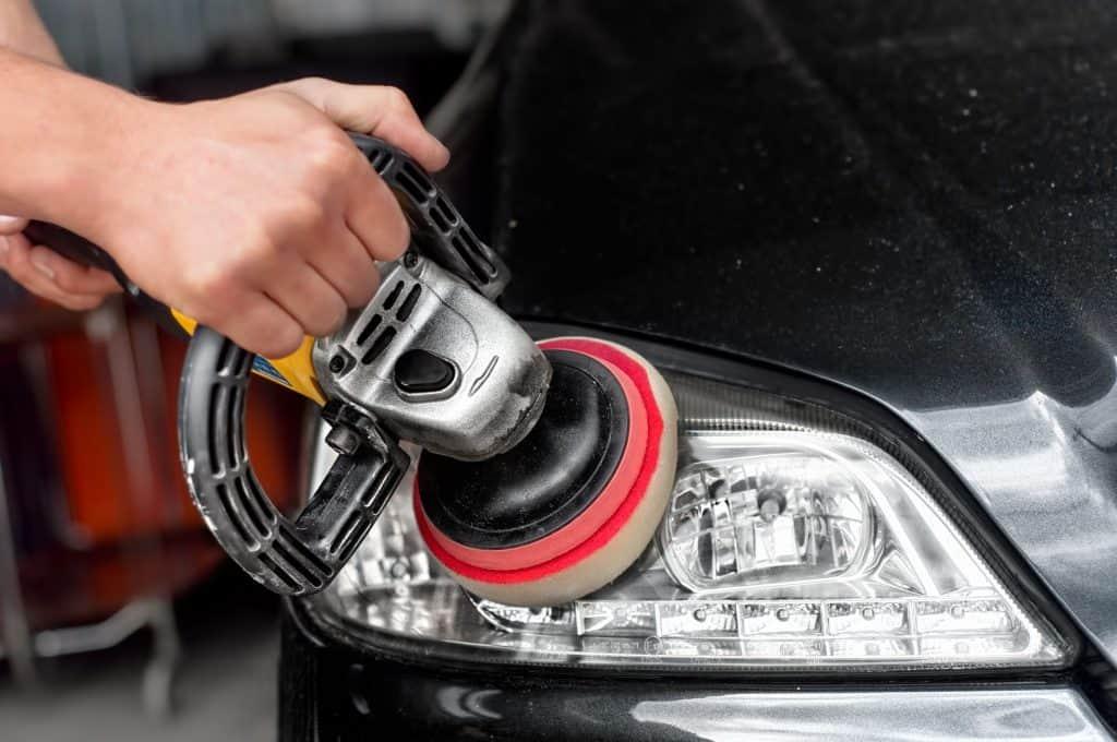 Imagem mostra o uso de uma politriz nos faróis de um automóvel.