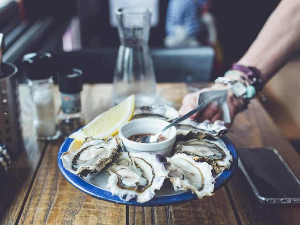 Mão segurando um prato cheio de ostras.