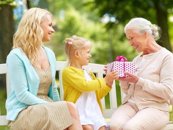 Na foto uma mulher, uma menina e uma senhora ganhando um presente, sentadas em um banco no parque.