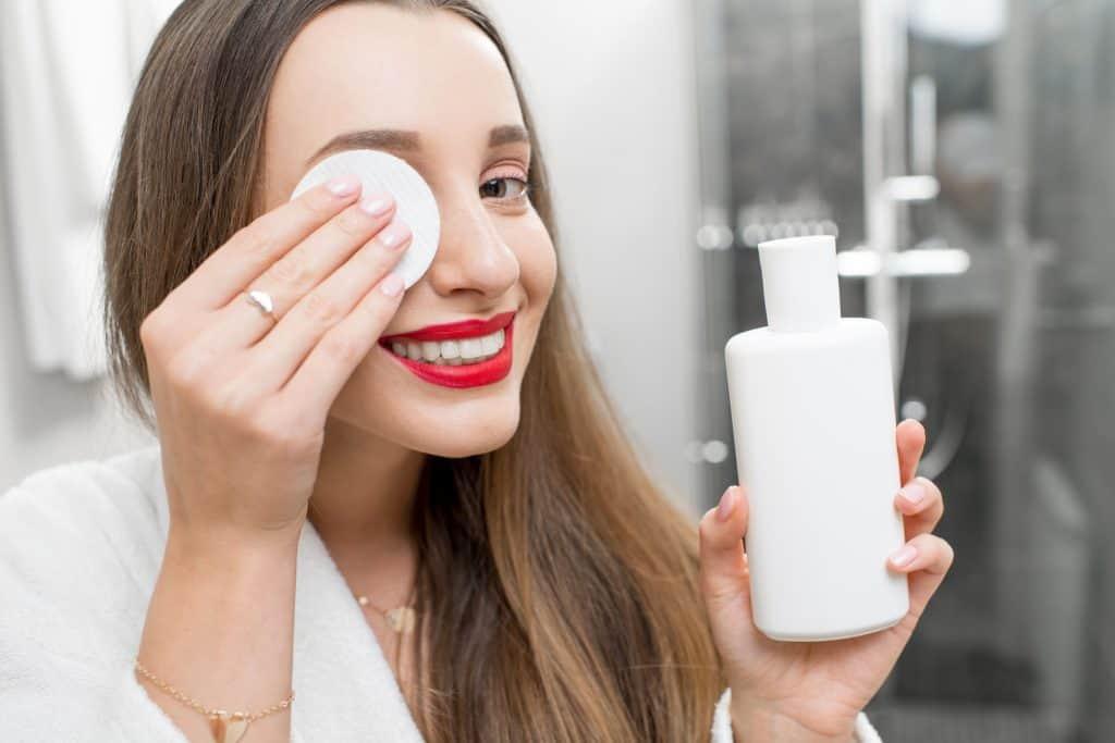 Mulher fazendo limpeza no rosto.