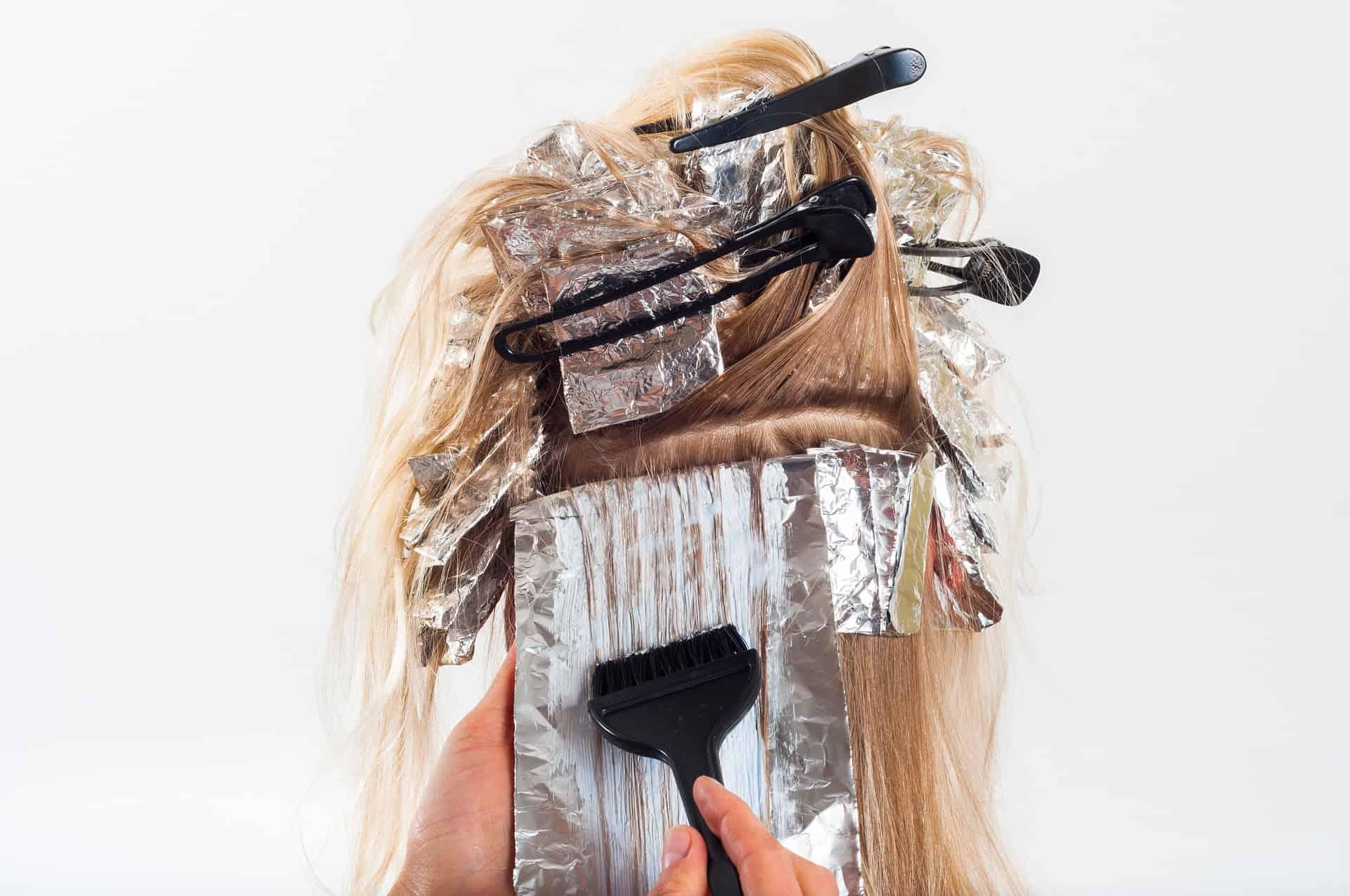 Cabeleireiro tingindo cabelo de mulher de loiro.