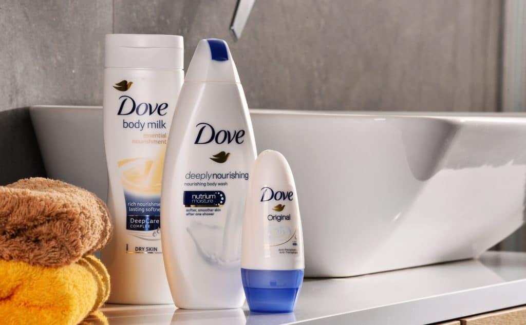 Bancada de banheiro com produtos Dove ao lado de pia e toalhas.