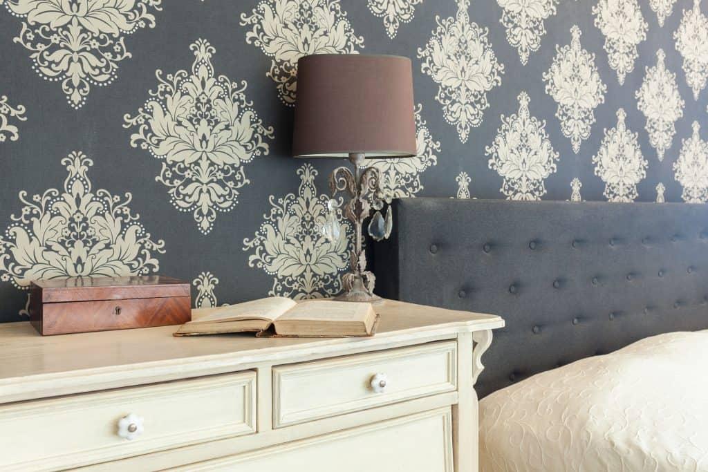 Cama e cômoda com papel de parede atrás.