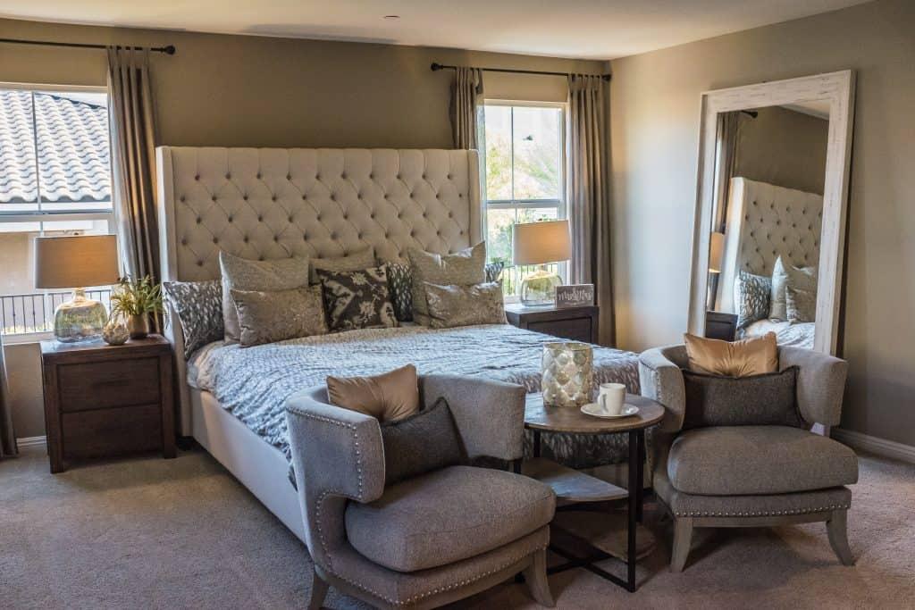 Na foto um quarto com móveis e peças em tons de madeira, cinza e branco.