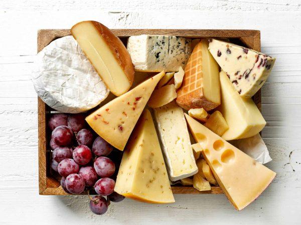 Na foto uma tábua de madeira com diversos tipos de queijo.