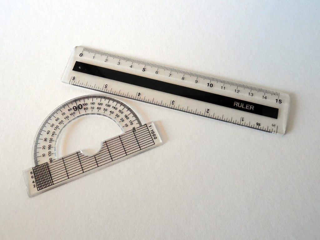 Imagem de um transferidor de grau ao lado de uma régua.