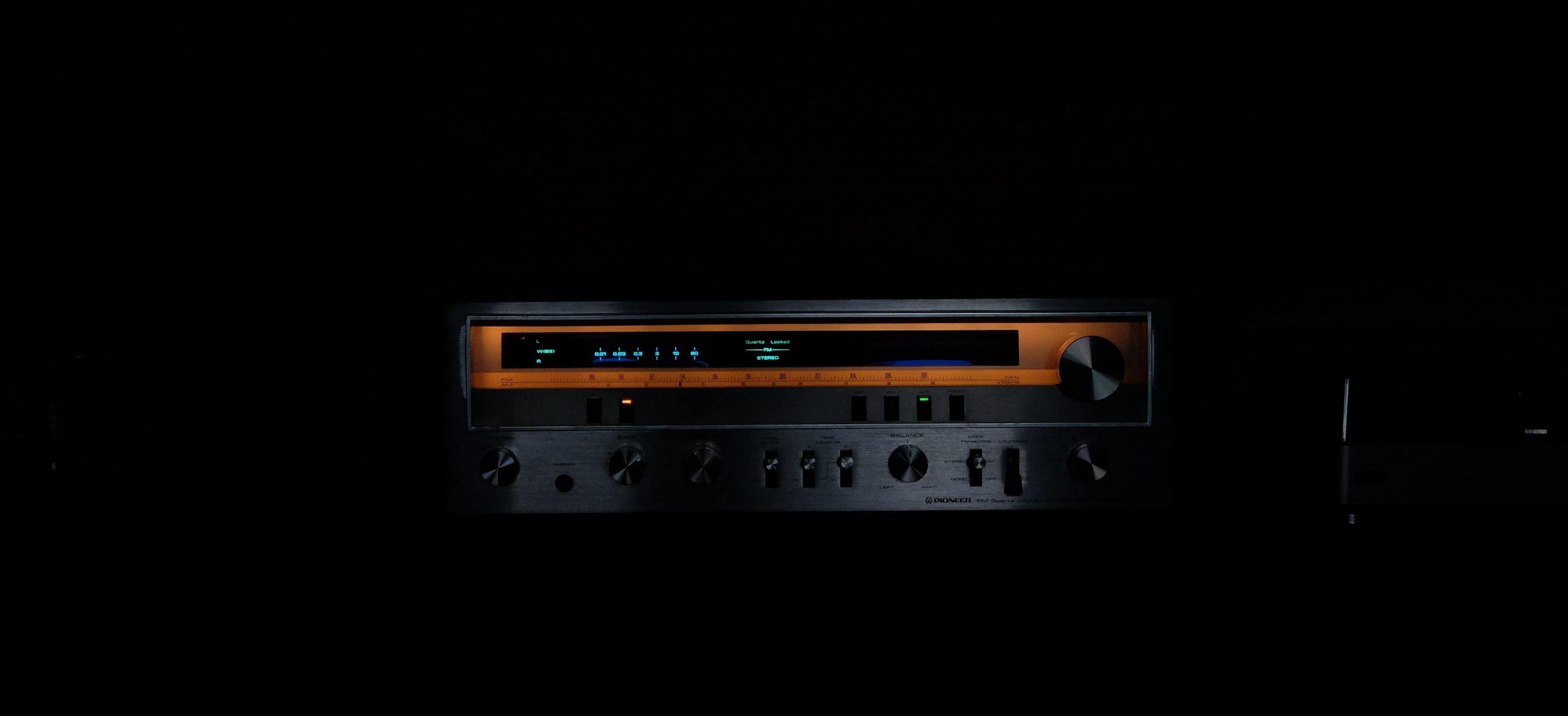 Imagem de receiver yamaha em fundo escuro.