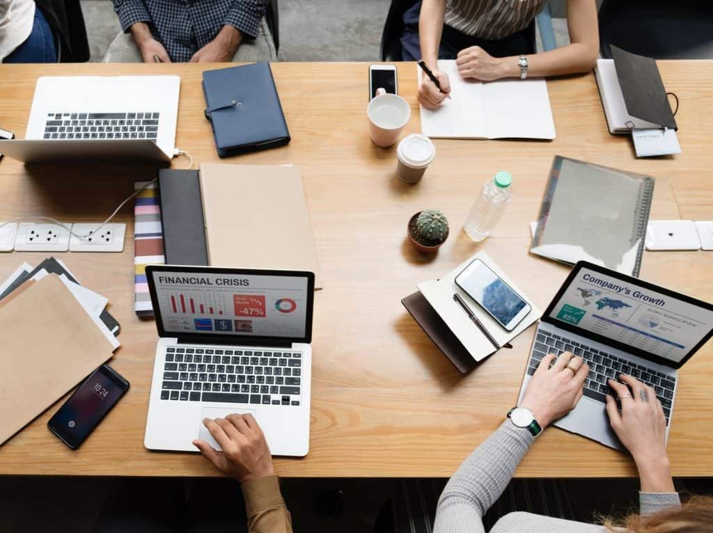 Imagem mostra uma mesa de trabalho com vários notebooks e pessoas em atividade.