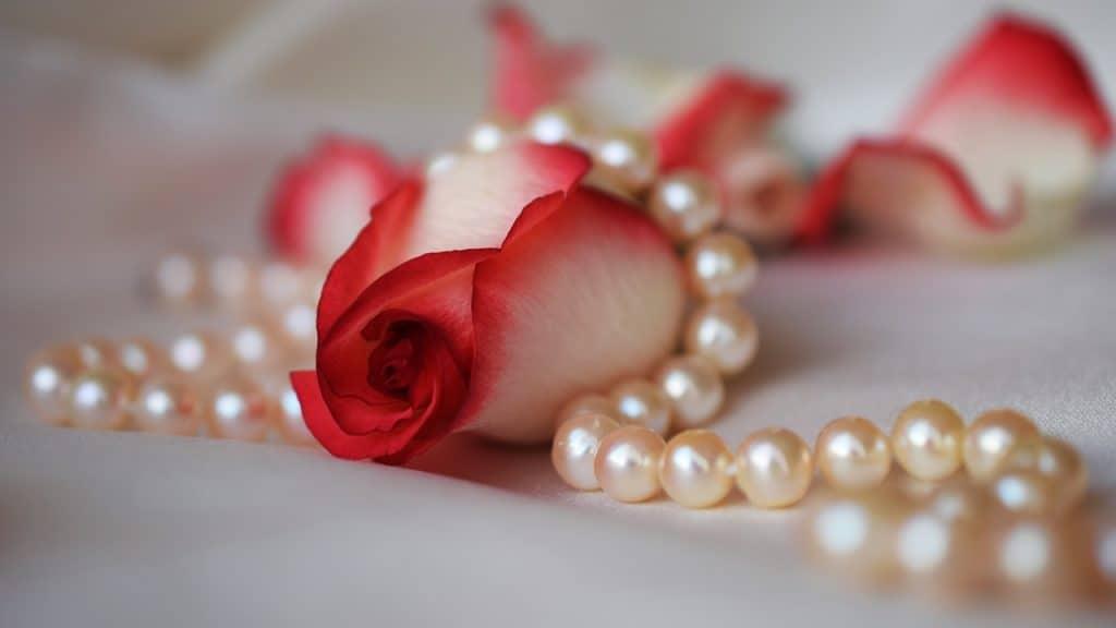 Imagem de rosas e terço de noiva em pérolas.