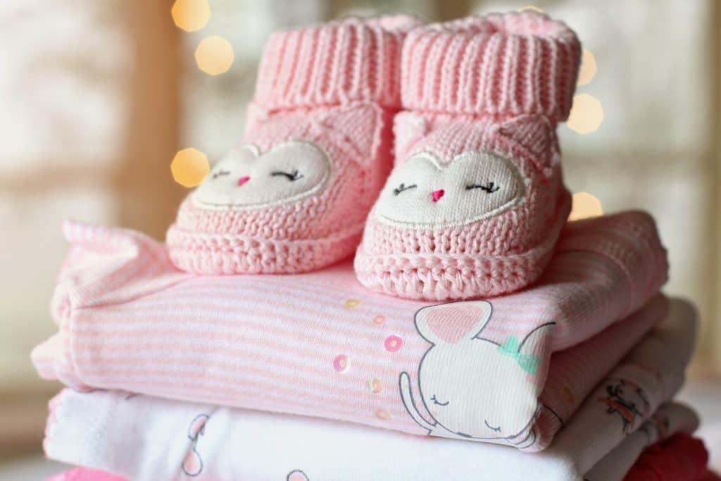Na foto uma pilha de roupinhas femininas de bebê com um sapatinho em cima.