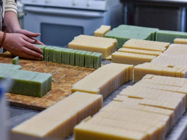 Mãos de pessoa organizando sabonetes artesanais em barra.