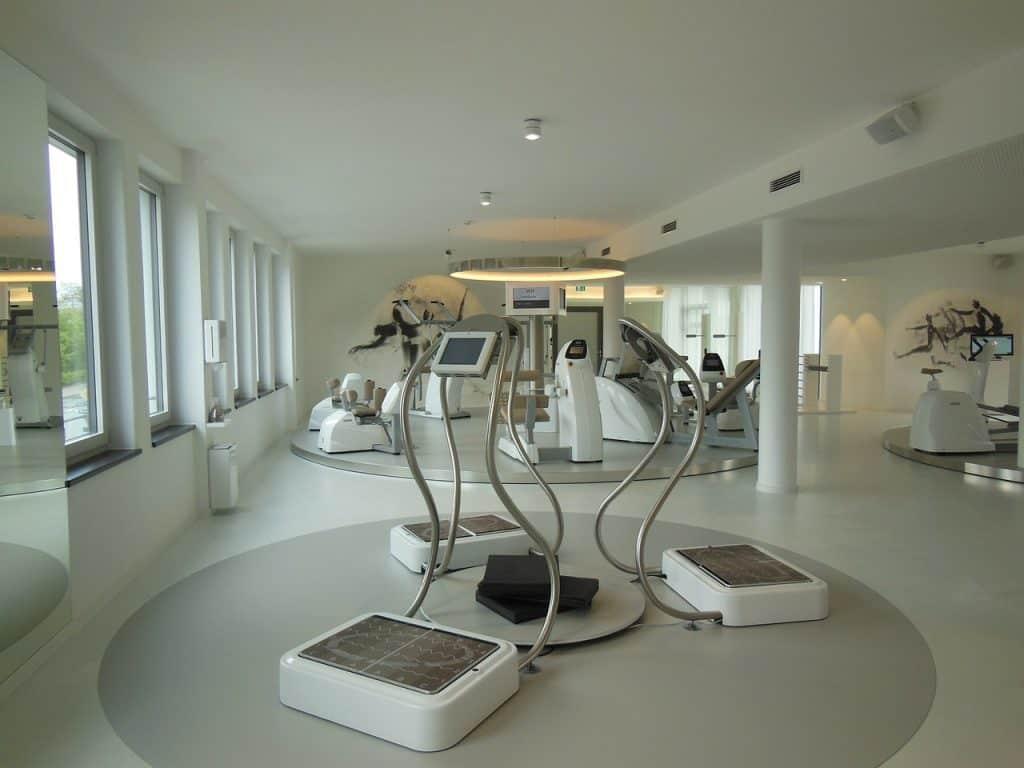 Na foto três plataformas vibratórias dentro de um estúdio de ginástica.
