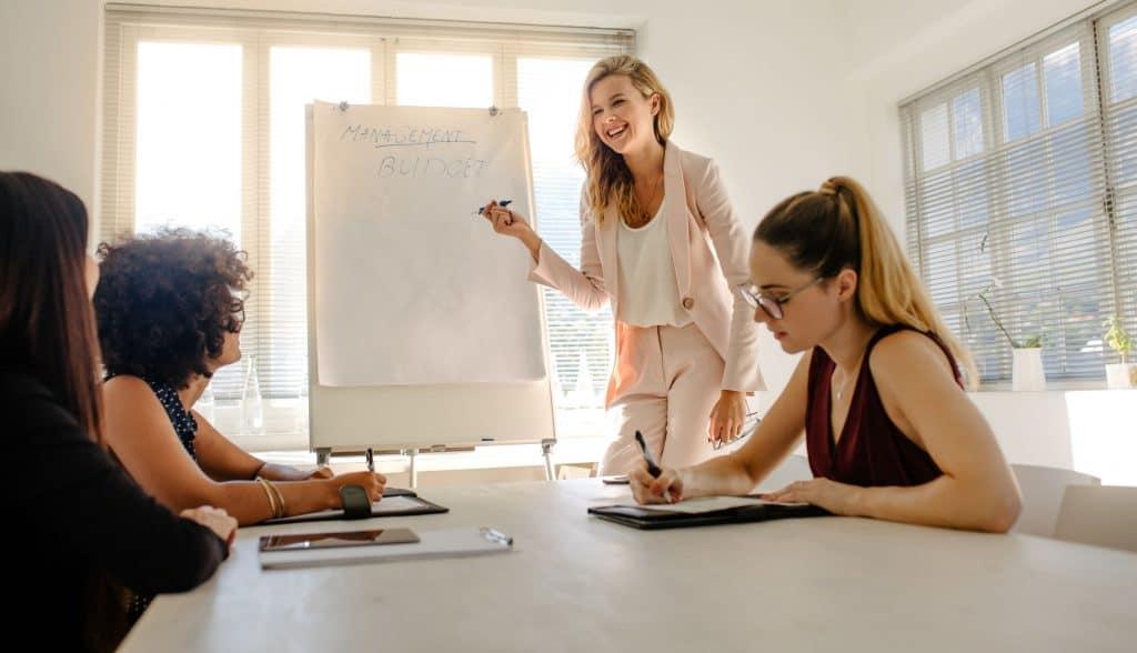 Na foto quatro mulheres em uma sala de reunião com um flip chart.