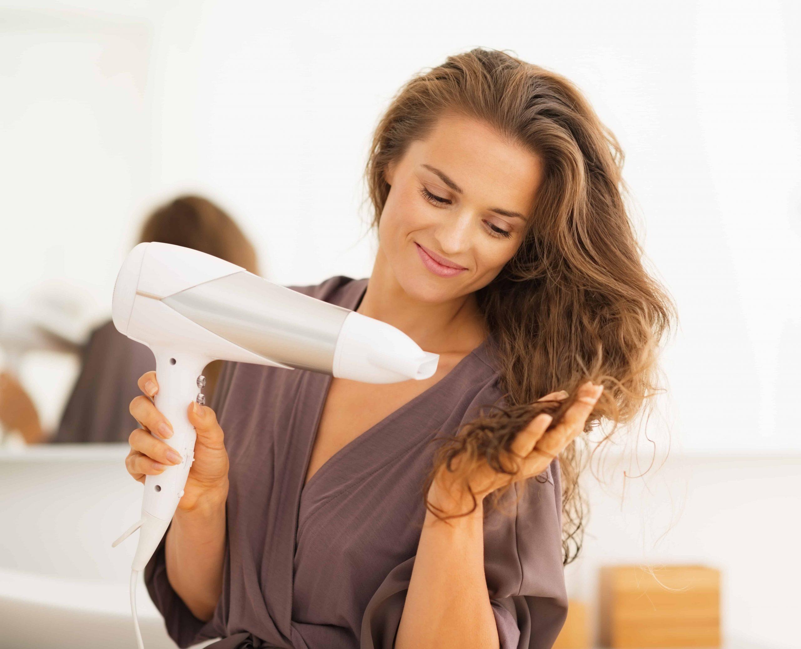 Mulher secando o cabelo.