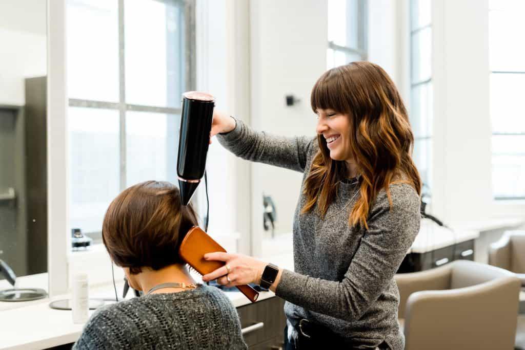 Imagem de uma cabeleireira secado o cabelo de uma cliente.