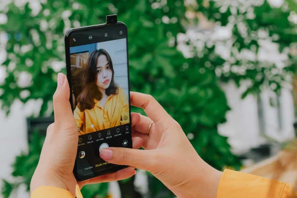 Imagem de uma menina tirando uma selfie.