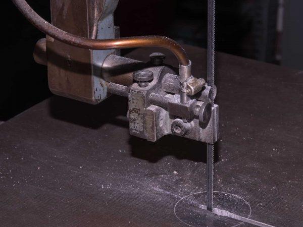 Uma serra de fita serrando uma tábua de madeira.