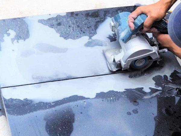 Imagem mostra uma pessoa usando uma serra mármore em uma peça de mármore.