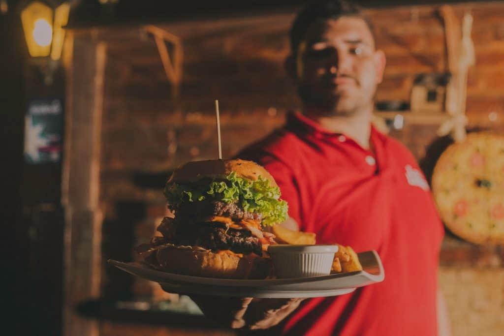 Na foto um homem segurando um prato com hambúrguer.