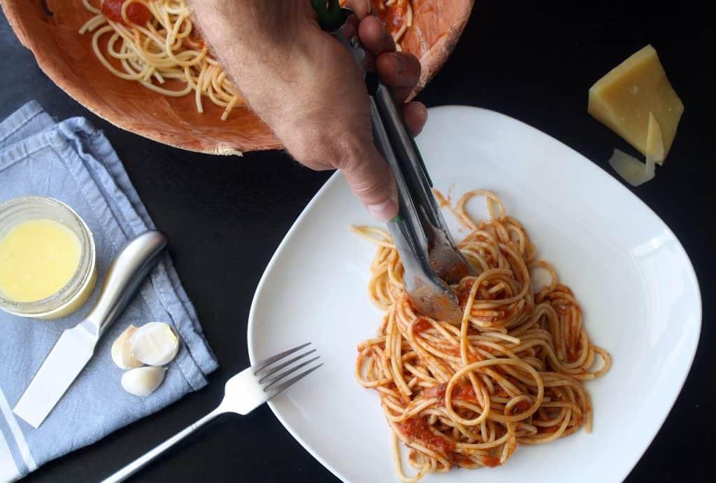 Pessoa serve espaguete em prato com auxílio de pegador de macarrão do tipo pinça.