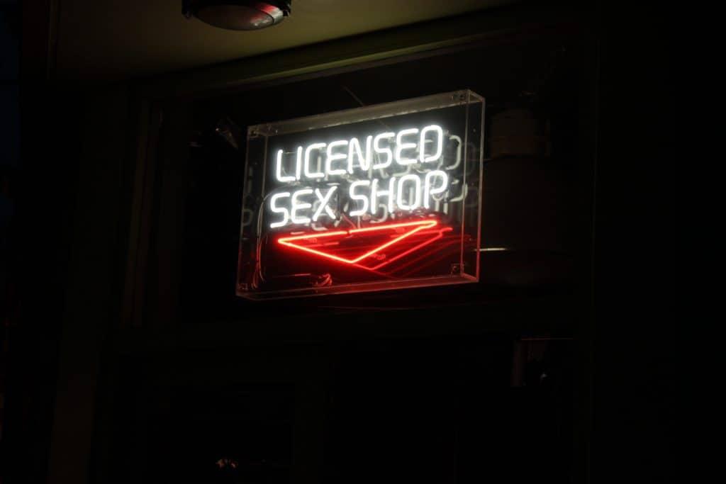 Imagem de letreiro neon de sex shop.