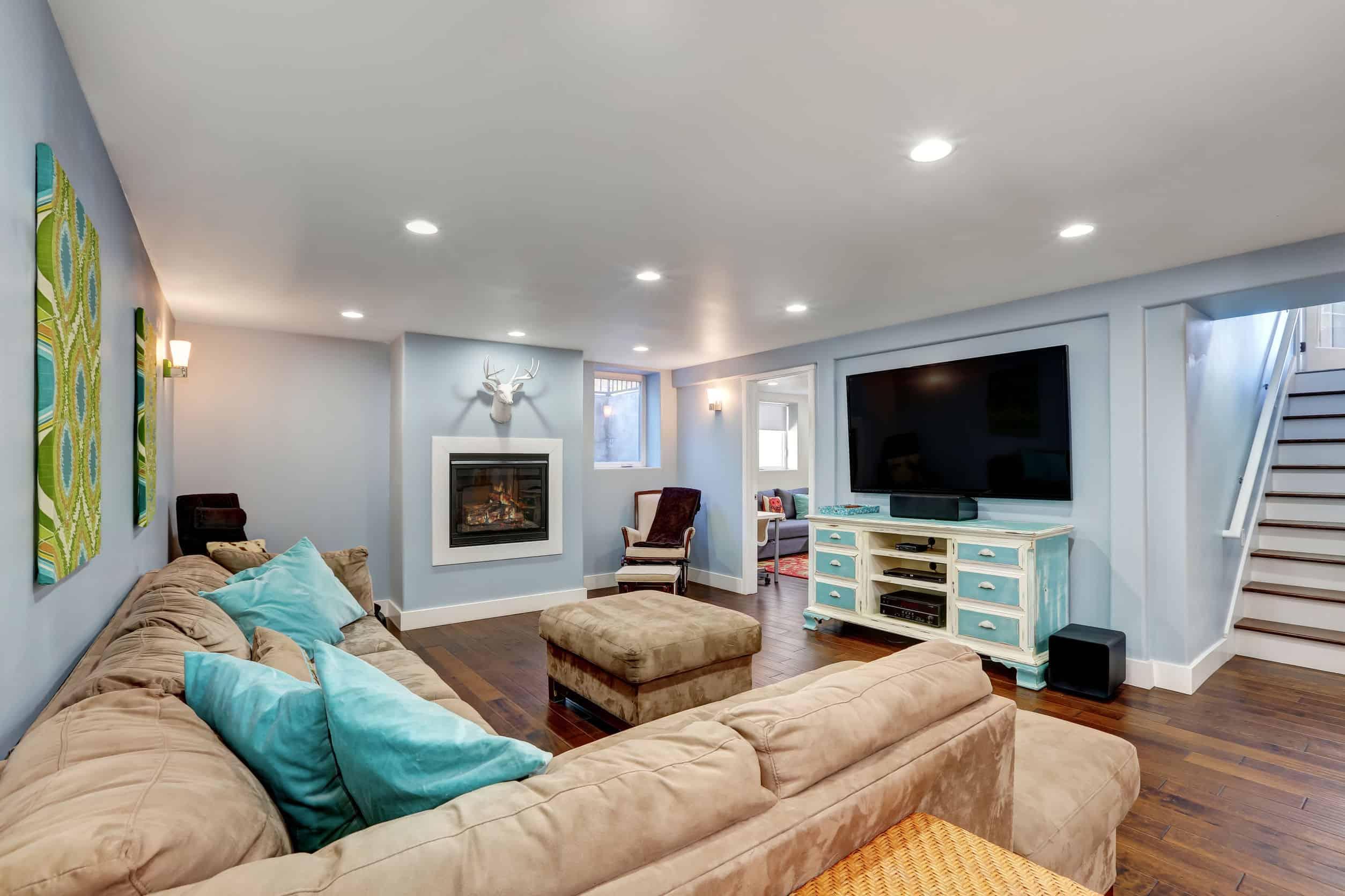 Na foto uma sala de estar com um sofá, lareira, televisão e uma escada ao lado direito.