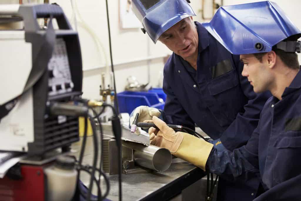 Dois homens trabalhando com máquina de solda.