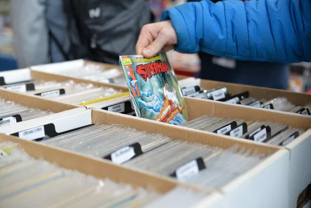 Um HQ do Superman sendo retirado por uma mão de uma caixa aberta com outros quadrinhos enfileirados.