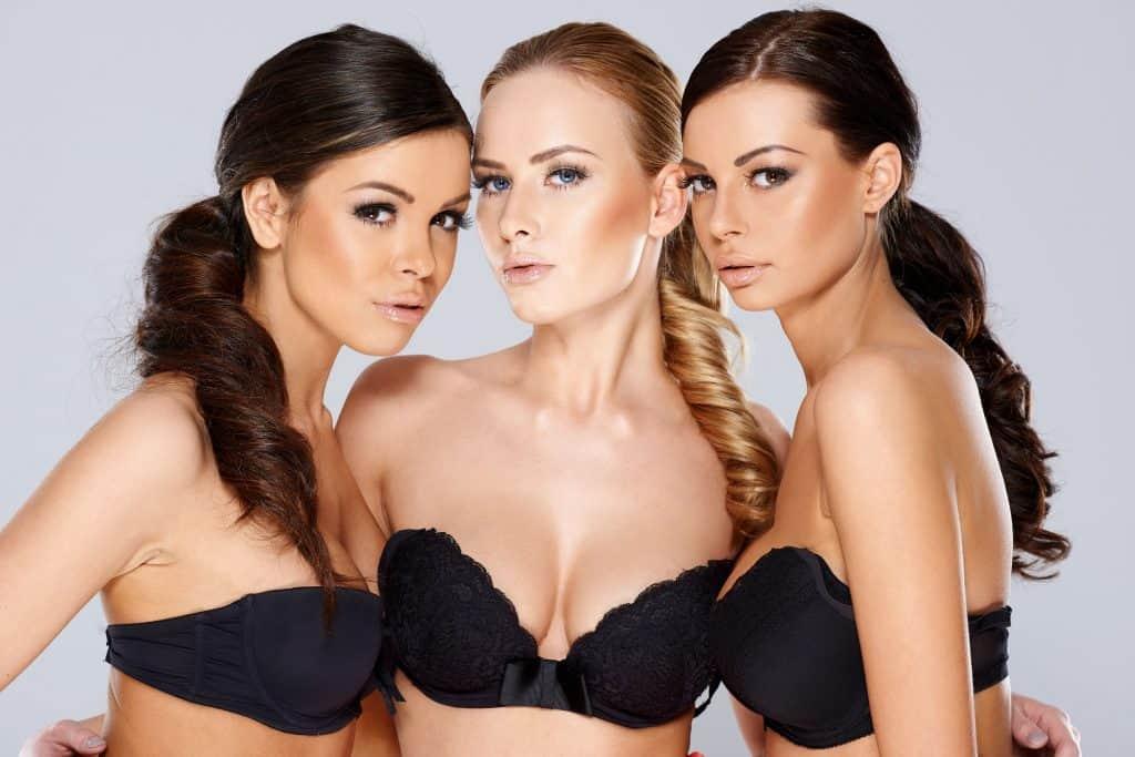 Foto de três mulheres vestindo sutiã tomara que caia preto.