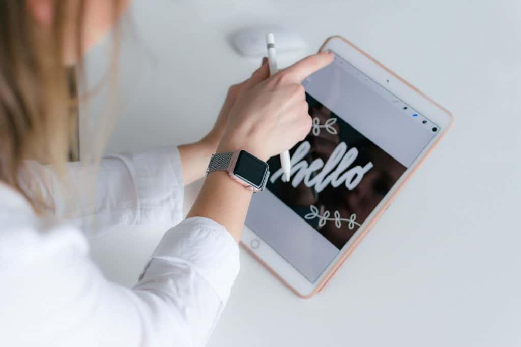 """Na foto uma mulher segurando um iPad escrito """"Hello"""" na tela."""