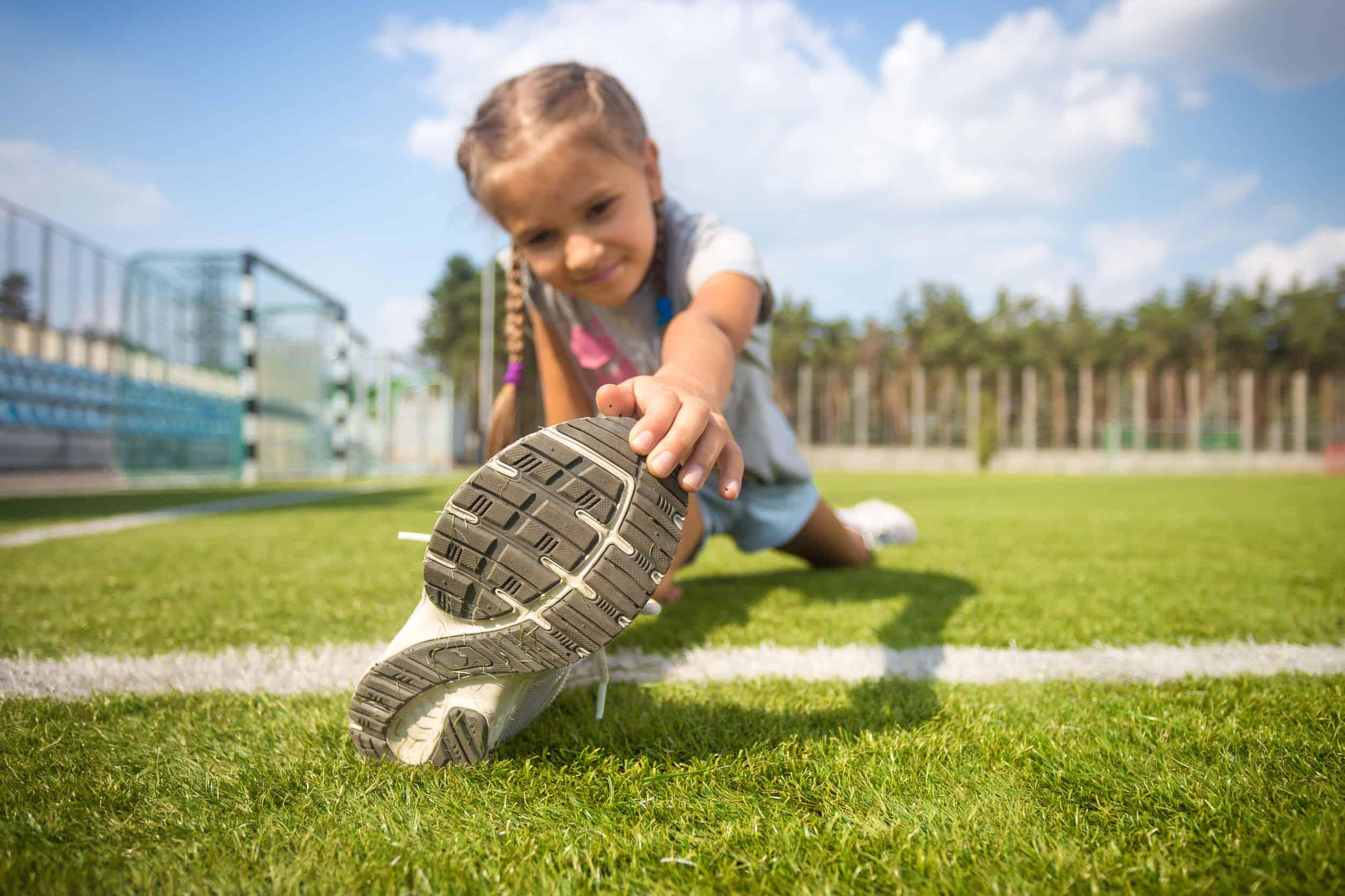 Na foto uma menina em um campo se alongando.