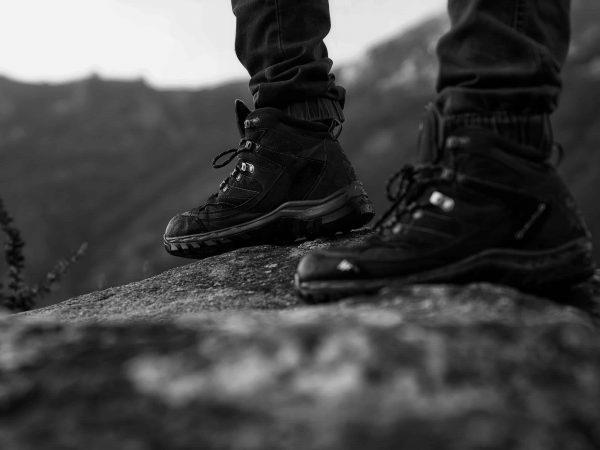 Imagem mostra apenas os pés de uma pessoa, que calçam botas modernas, apoiadas sobre uma rocha. Ao fundo, uma montanha, desfocada.