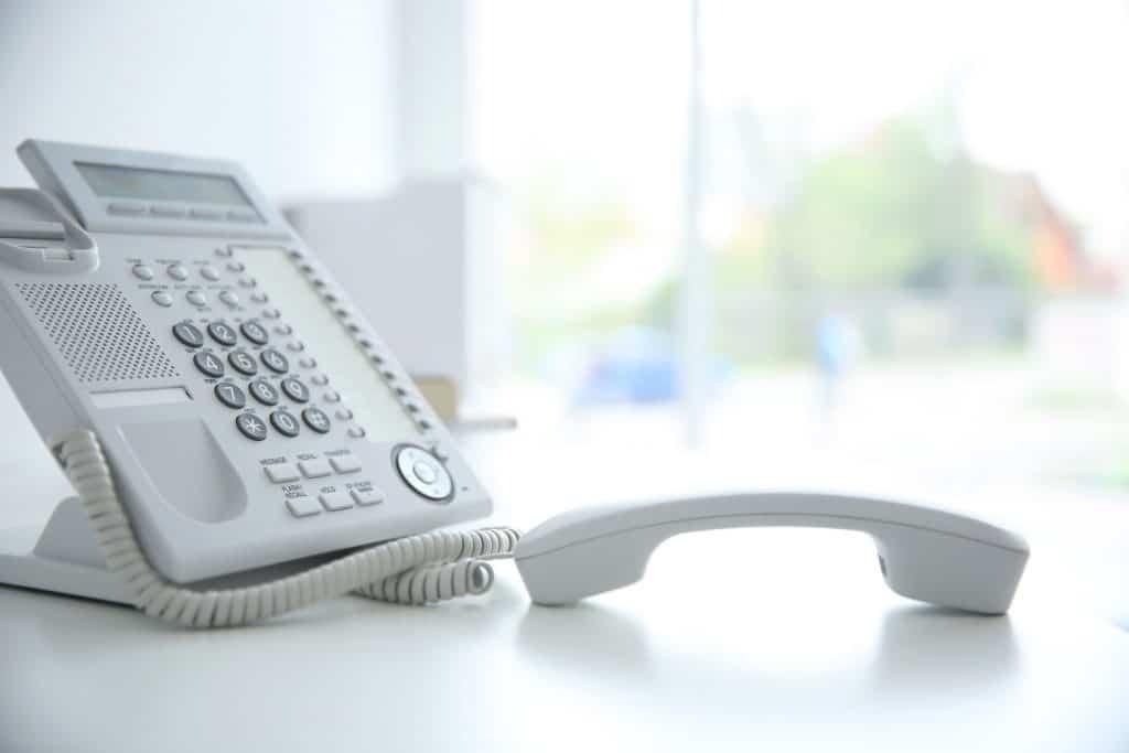 Na foto um telefone branco em cima de uma mesa em uma sala vazia.
