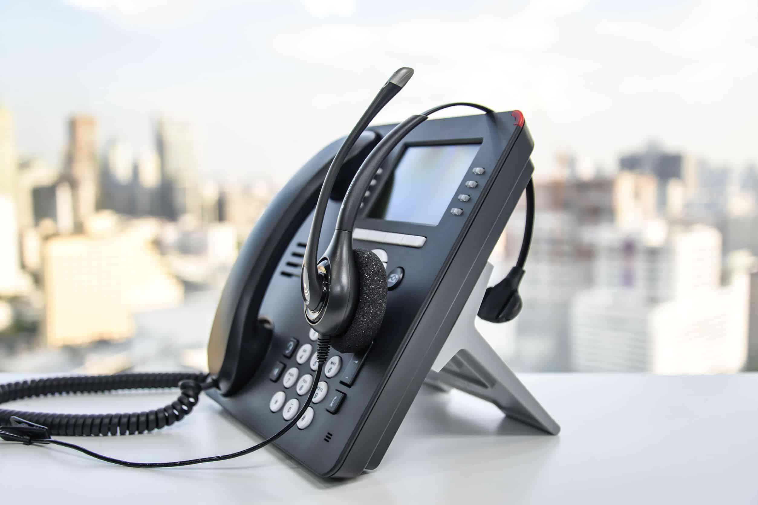Na foto um telefone IP em cima de uma mesa com uma cidade ao fundo.