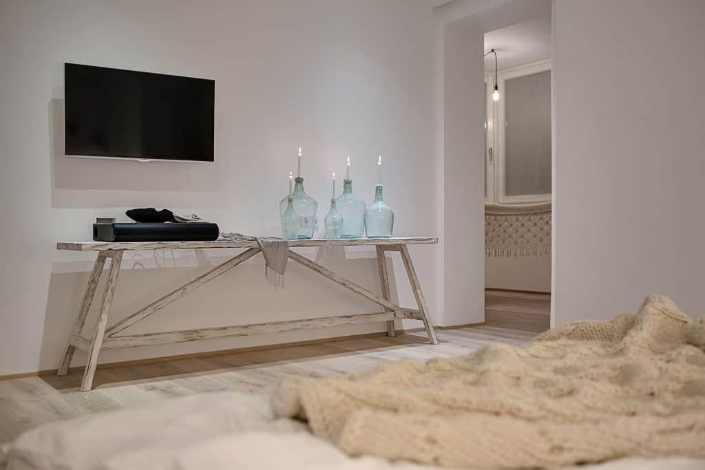 Uma tela pendurada na parede branca. Abaixo existe uma mesa com uma soundbar acima. Mais para frente tem uma cama com cobertor. O cenário é um quarto de casal.